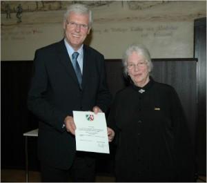 Regierungspräsident Dr. Peter Paziorek überreicht die staatliche Anerkennungsurkunde an die Kuratoriumsvorsitzende Marianne Ellermann.